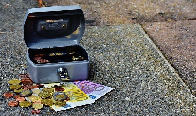 mała otwierana skarbonka z wyjętymi banknotami i bilonem w różnej walucie