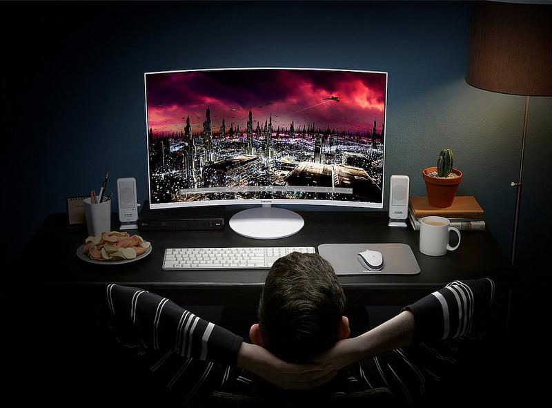 curved monitor 24 cale a przed nim siedzi młody człowiek i ogląda na nim film